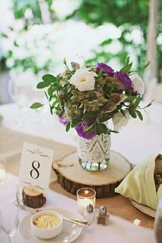 August wedding centerpiece with baptisa greens, mountain mint, dusty miller, and lisianthus.