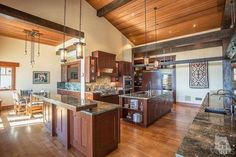 Fabulous Craftsman style kitchen with massive ceiling beams, distinctive light fixtures, warm woods, and exquisite granite.