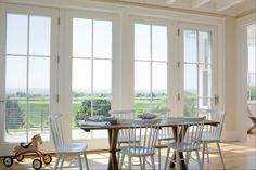 Gorgeous beach house dining room with French doors framing ocean view. Salvaged wood x-base dining table paired with DWR White Salt Chairs and light hardwood floors.