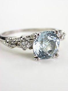 Vintage Platinum Aquamarine Engagement Ring Four diamonds on the shoulders of this aquamarine engagement ring add radiance to the polished band. Details: Vintage. Circa 1930 or later. Platinum. Round brilliant cut diamonds; 0.30 carats. Round cut aquamarine; 1.83 carats. Ring Size 7.0.