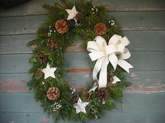 Fresh assorted evergreen Oval wreath decorated with birch bark stars, pine cones and babies breath.