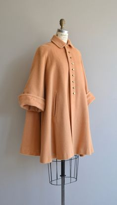 Its amazing, the movement of it is like no modern coat you will find - vintage 1950s butterscotch wool swing coat with high buttoning collar, brass buttons, top decorative button, very wide sleeves (can be worn cuffed), enormous sweep, welt pockets and turquoise polka dot silk crepe lining. Super warm.  --- M E A S U R E M E N T S ---  fits like: medium/large shoulder: n/a, raglan sleeve bust: free waist: free hip: free sleeve: approx. 20 length: 36 66 sweep! brand/maker: n&#x2...