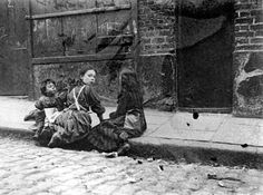 Three young girls in the slums, Twine Court, London circa 1900