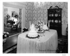 The dining room table is covered in white tulle, and features candles lilies, and two decorated wedding cakes, one for the bride, one for the groom. A small chandelier hangs above the table; adjacent to the table is a large china cabinet. In the adjoining room, floral arrangements are visible on either side of the home furnishings.