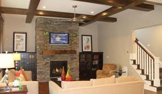 dark wood ceiling beams, stacked stone fireplace, and rustic wood mantle