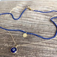 "Tiny matte blue seed beads are strung with a tiny gold disc and then layered with a blue evil eye pendant on heavy chain. The lobster closure, chain, and other components are gold-filled, and the pendants are gold plated. The lengths are 15"" and 17"". Also available in black - choose that option at checkout. Your necklace will come with a gift box + ribbon // Made with ♥ + quality materials!"