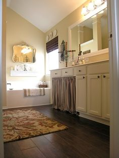 Lovin' the tile that looks like wood, the idea of the mirror over the tub, and the fabric under the vanity.