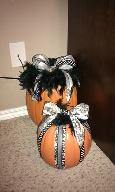 Pumpkins with ribbon and feathers.