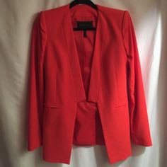 """BCBG Max Azria """"Andres"""" poppy red blazer Very chic and tailored poppy red blazer by BCBG Max Azria. Can be worn with dress pants, pencil skirts, blouses, or even with dressy leggings. It has flat lapels with a clasp at the end and one slit pocket on each side. The back also features a slit. It also has shoulder pads. It is mostly made of polyester and rayon and has a satin lining. Worn twice. In amazing condition. Fits a 00 or 0. I'm a 2 and it fits but I have a smaller chest. BCBGMaxAzria…"""
