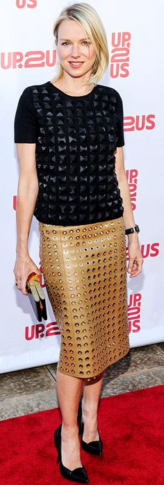 Who made Naomi Watts's tan skirt, black studded short sleeve top, and black pumps? Shirt and skirt – Burberry  Shoes – Proenza Schouler