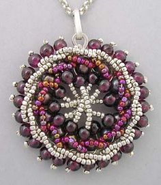 Silver and Garnet Circular Pendant from Eni Oken's Jewelry.   Garnets, pearls, sterling silver seed beads and charlotte iridescent beads are threaded with sterling silver wire to a sterling silver back ring using handmade lace techniques.