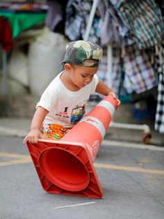 The boy thought the traffic cone did not belong into the street