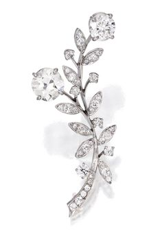 BROOCH, VAN CLEEF & ARPELS The foliate spray set with two round diamonds weighing approximately 2.55 and 1.35 carats, accented by numerous round, old European and single- cut diamonds weighing approximately 1.20 carats, signed V.C., numbered 25159 SO.