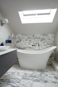 Fürdőszoba tetőtérben, a ferde tetősík és tetőablak alatt szabadon álló kád