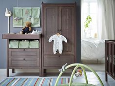 A baby room with grey-brown SUNDVIK changing table, wardrobe and crib