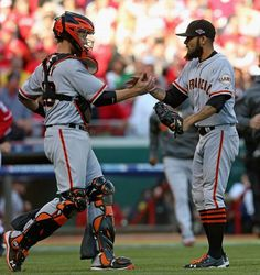 Buster Posey #28 and Sergio Romo #54 of the San Francisco Giants shake hands after a win against the Cincinnati Reds in Game Five of the National League Division Series at the Great American Ball Park on October 11, 2012 in Cincinnati, Ohio. The Giants defeated the Reds 6-4.