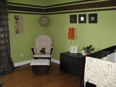 painted with Dill Pickle paint color by Benjamin Moore. Brown is the perfect accent color to green. The trio of brown stripes is a wonderful display of a 2nd accent color to the walls. Loving the orange pop with the lamp shade.