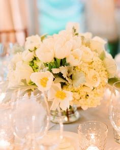 Arrangements of tulips, hydrangeas, roses, and lamb's ears were surrounded by small glass votives.