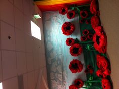 Wizard of Oz: Poppy Field Tissue paper flowers hot glued inside large clear catering container toppers. Tall standing flowers built the same, but attached to long stands made out of formed chicken wire lined with green crepe paper.