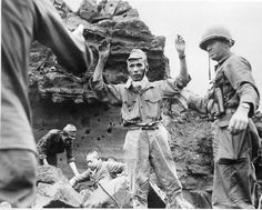 Japanese soldiers being taken prisoner after hiding for 20 days-or so in the caves on Iwo Jima