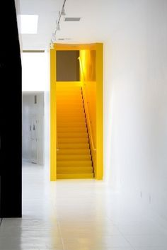 Yellow staircase and white walls creates a very clean and fresh look - interior design