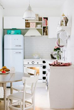 All white kitchen with vintage refrigerator and oven with pink accents.