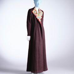 The evening coat was worn in the autumn/winter of 1936 containing dark red wool and a collar of velvet appliqués with gold leather and beads.