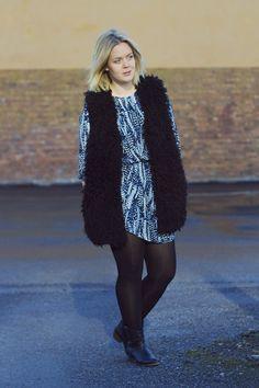 Spring style outfit: printed blue dress, faux fur vest, cowboy boots