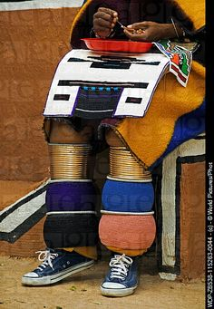 Africa | Ndebele woman in traditional dress showing brightly coloured multiple leg bands of a married woman Lesedi Cultural Village near Johannesburg, South Africa | ©World Pictures