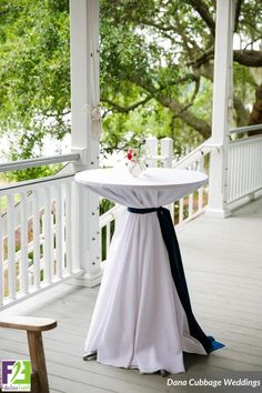 A white polyester linen with a navy sash can turn a boring old cocktail table into a more elegant look! | Fabulous Events    #FabulousEvents #CocktailTable #Weddings #CocktailHour #HappyHour #NavySash #WhiteLinen