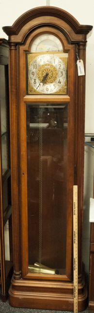 HOWARD MILLER PENDULUM GRANDFATHER CLOCK WITH THREE CHIMES IN OAK CASE. MAKERS TAG WITH SERIAL NUMBER IS ON THE INSIDE OF THE DOOR. MEASURES 6 FT 8 IN. H X 24 IN. W X 14 IN. D.