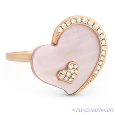 The featured ring is cast in 14k rose gold and showcases a flat heart-shaped mother-of-pearl held by a crescent outline & topped with a heart design both accentuated with round cut diamonds.
