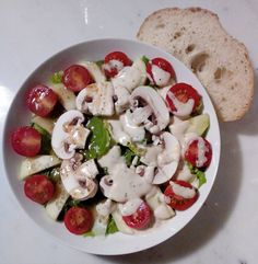 Homemade Garden Delight Salad! Romaine lettuce, organic cherry tomatoes, cucumber, & mushrooms w/ half Caesar & half red wine & olive oil dressing w/ a side of sourdough bread.