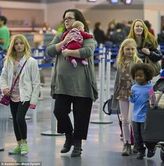 'Back in Miami': Rosie O'Donnell cradled her adopted daughter Dakota alongside her family at JFK Airport in New York Monday