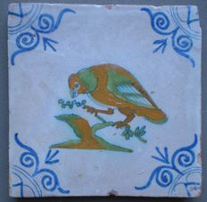 Antieke tegel met Papegaai hoekmotief ossekop  ( zeldzame voorstelling )