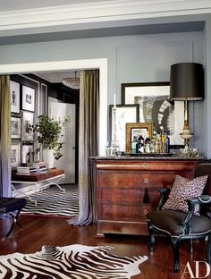 A doorway is framed by Restoration Hardware linen curtains customized with a border from M&J Trimming | archdigest.com