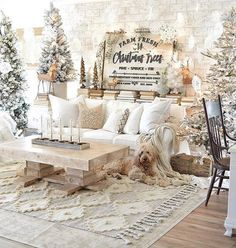Neutral farmhouse style Christmas decor at its finest by Natalie Love the textured rug flocked trees and hanging snowflakes from the ceiling.