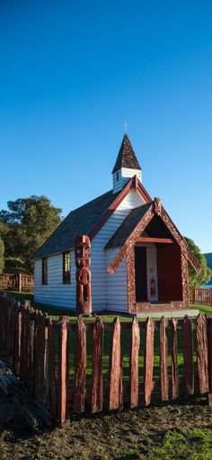 Old Onuku Maori Church with rough red wooden fence and carvings - Akaroa Harbour , NZ