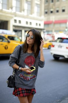 Grey 3/4 Sleeve Spider-man Graphic Shirt, Plaid Red Skirt, Ombre Hair, Shoulder Length Haircut, Black Purse, Round Sunglasses, Bangles, Arm Tattoo.