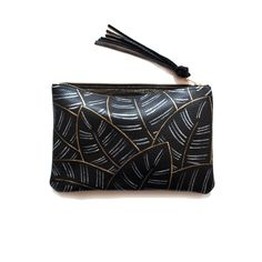 """painted calathea leather clutch - kermis $128 Inspired by leaves of the Calathea majestica plant, hand-painted with repeating gold + silver leaf pattern. perfect size for stashing essentials or for carrying along to evening events.  beautiful pebble-grained black cowhide leather.  Knotted leather zipper pull.   Lined with metallic linen.  - Gold zipper. 10.5 x 7.5"""" painted by hand, making each one unique. For this reason, the leaf pattern may vary slightly from the item pictured."""