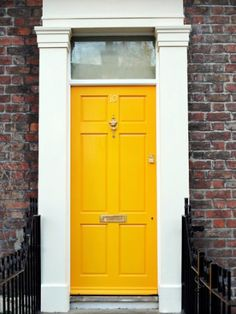A splash of sunshine adds polish this home's faded brick facade. See more colorful doors >>