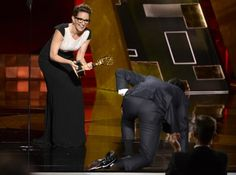 Hamm crawls on stage to accept the award from Tina Fey.