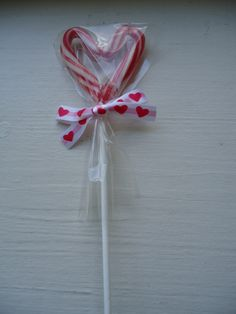 What might be the ultimate Valentine craft made from Christmas items? Candy Cane Heart Pops!!! Place mini candy canes in heart fashion onto parchment paper lined cookie sheet & bake at 300 F for about 5 minutes (check often). When the candy canes just start to melt remove & add the lollypop sticks, pinching the candy cane ends over the pop stick. Remove lollypop from parchment paper when cooled; wrap in cellophane & tie with ribbon!