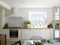 Cream kitchen with white metro tiles, oak work top and wood floor