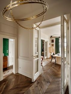 House tour: a 1930s Parisian-style apartment in Warsaw: In the hallway, brass 'Citadel' chandelier by QUASAR; brass hardware on doors by LINEA CALI; custom-mixed white paint created by Chrapka using FARROW & BALL; green malachite wallpaper by COLE AND SON, seen through open doorway.