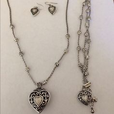 Brighton jewelry set Necklace is reversible and 10-11 inches long with pendant included. Bracelet is 8 inches long, has same charm as necklace and is is triple layered. Appears that the charm has one missing stone/crystal in it. Earring have same design but also have a hint of gold in them. Brighton Jewelry Necklaces