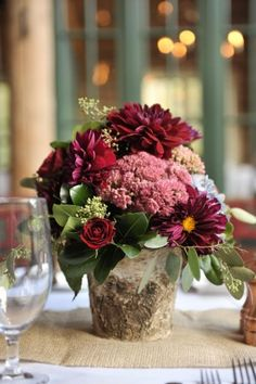 centerpieces of elegant blue hydrangea and burgundy dahlias were placed in natural bark-wrapped vases