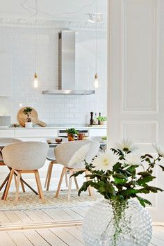 This white kitchen is calming especially when furnished with white chairs and a wooden floor.