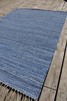 . . Man kan nästan tro att det är ett glittrande somrigt hav, men det är en matta i gåsögon med jeans och linvarp. Den första mattan j...