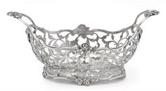 A FINE DUTCH SILVER BASKET  MARK OF WIJNAND WARNEKE, AMSTERDAM, 1773  Shaped oval, on four flowering feet, the body pierced and engraved with flowers and scrolls, with two everted foliate handles, marked under base  7 3/8 in. (18.7 cm.) long; 5 oz. 10 dwt. (181 gr.)